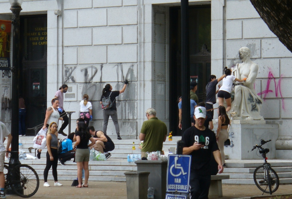volunteers try to remove paint defacing the Supreme Court Building in Sacramento