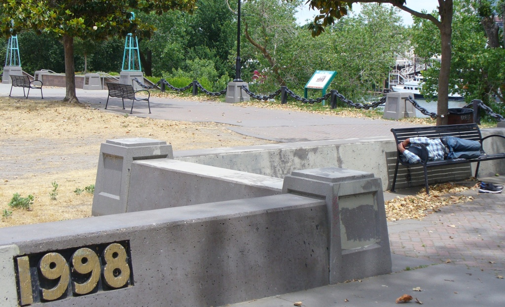 Man sleeps on bench at entry to West Sac riverfront walk
